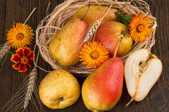 Pears decorated with flowers and wheat on old wooden background Stock Photos
