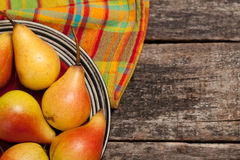 Pears on the dish and cloth on the old wood backing Stock Images