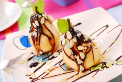 Pears with flaked almonds and chocolate sauce. Two pears with flaked almonds poured chocolate sauce Stock Photos