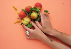 The pears with a hand on the peachy flat. Royalty Free Stock Image