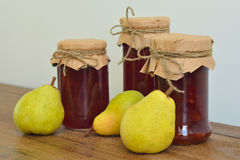 Pears and homemade jam. Pears and glass jars of jam on the table royalty free stock photo