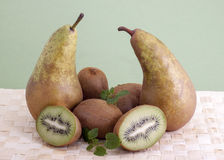 Pears and kiwi . Pears and kiwi fruit on a bamboo napkin on a green background Royalty Free Stock Photos