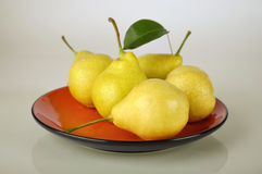 Pears on orange plate Royalty Free Stock Photos