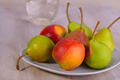 Pears with peaches on a plate Royalty Free Stock Photography