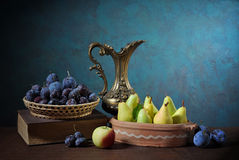 Pears, plums, books and a metal carafe Stock Photos