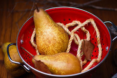 Pears on red colander Stock Images