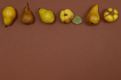 Pears in row on brown background with copy space Royalty Free Stock Photos