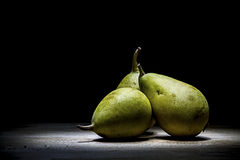 Pears. Three pears on a wooden shelf photographed with the technique of lightpainting Royalty Free Stock Photography
