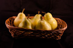Pears. Wicker basket of pears with background black Stock Photo