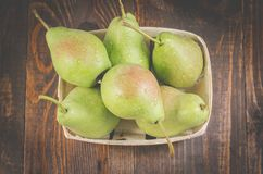 Pears in a wooden box on a dark background/ripe pears in a wattled box on a wooden background, top view royalty free stock images