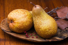 Pears on wooden plate Stock Photos