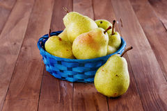 Pears in a woven basket on wooden background. Group of juicy yellow pears in a blue woven basket on a wooden background royalty free stock photography