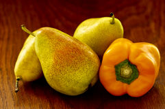 Pears and a yellow pepper on a wooden background Royalty Free Stock Image