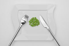 The peas. A bunch of peas on a white plate with fork and knife Stock Photo