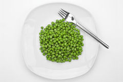 The peas. A bunch of peas on a white plate with a fork Royalty Free Stock Image