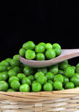 Peas. Fresh wet green peas on the wooden spoon Stock Photos