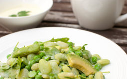 Peas, arugula and avocado salad with creamy dressing. Green peas, arugula and avocado salad with creamy dressing stock images