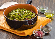 Peas with bacon in terracotta bowl. Stock Photography