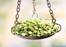 Peas in balance scale Royalty Free Stock Photo