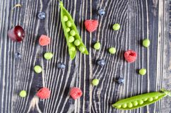 Peas and berries on a black wooden background royalty free stock photo