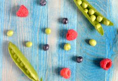 Peas and berries on a blue wooden background royalty free stock images
