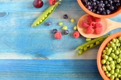 Peas and berries on a blue wooden background stock images