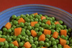 Peas and carrots. A bowl of healthy food or a metaphor for things that are alike or close together Royalty Free Stock Photo