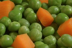 Peas and carrots. A bowl of healthy food or a metaphor for things alike or close together Royalty Free Stock Image