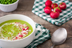 Peas cream with radishes on rustic wooden table. Fresh Peas cream with radishes on rustic wooden table Royalty Free Stock Photo