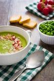 Peas cream with radishes on wood. Homemade peas cream with radishes on wood Stock Images