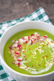 Peas cream with radishes on wood. Homemade peas cream with radishes on wood Royalty Free Stock Image