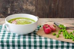Peas cream with radishes on wood. Homemade Peas cream with radishes on wood Royalty Free Stock Photos