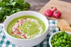 Peas cream with radishes on wood. Homemade Peas cream with radishes on wood Stock Photography