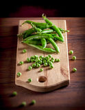 Peas on cutting board. On wooden table and dark background Royalty Free Stock Photos