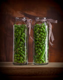 Peas in glass jars. On wooden box and dark background Stock Images