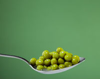Peas in metal spoon Royalty Free Stock Photography
