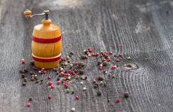 Peas pepper and pepper mill on the table Royalty Free Stock Image