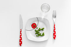 Peas on a plate with a glass of water, dieting concept Royalty Free Stock Images