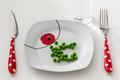 Peas on a plate with a glass of water, dieting concept Stock Image