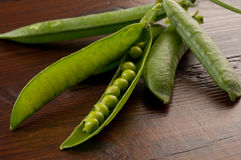 Peas pod open on wood Royalty Free Stock Photo
