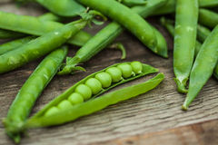 Peas in a pod shot on wood one open with visible peas. Stock Images