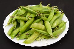 Peas pods on a white plate. On a black background Royalty Free Stock Photo