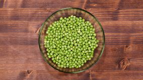 Peas slowly fill a glass bowl on the table stock footage
