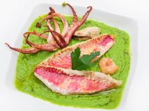Peas soup with mullet fillet and tentacles of squid Stock Image