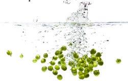 Peas splashing Stock Images