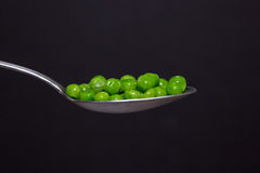 Peas on spoon Stock Photo