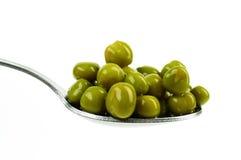 peas on a spoon detail Stock Photos