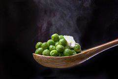 Peas on spoon topped with butter. Stock Images