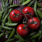 Peas and tomatoes. Whole peas and tomatoes top view Stock Image