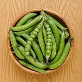 Peas. Top view of wooden bowl full of fresh peas Royalty Free Stock Image